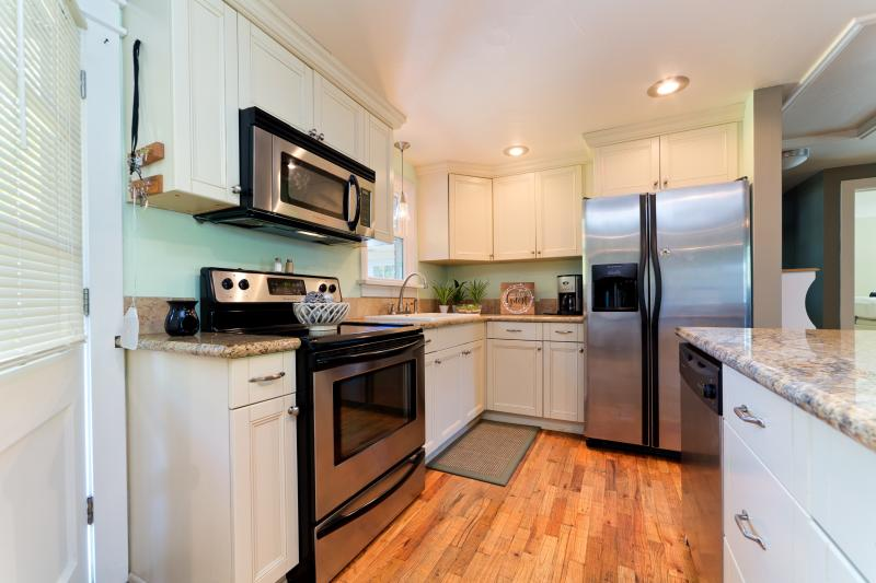 Pottery-Barn Style Kitchen  Stainless steel appliances equipped with cooking utensils pots & pans