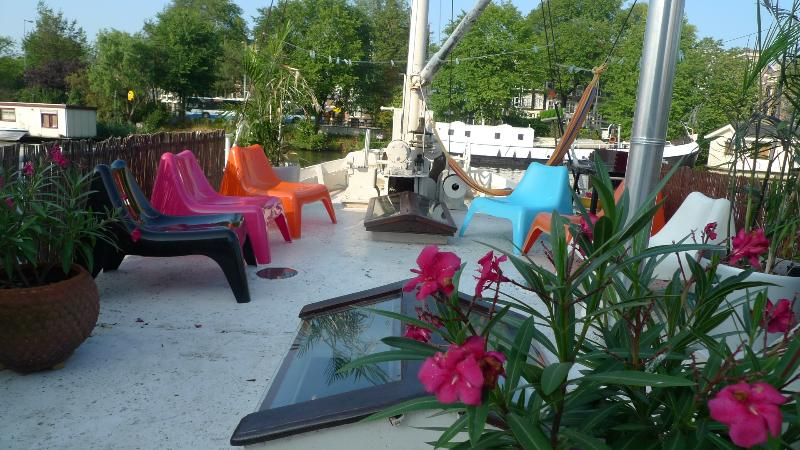 Sunny deck with chairs, hammock, plants and BBQ