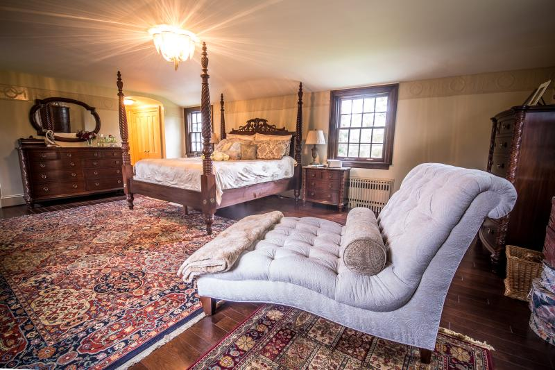 Master bedroom with Stickley furniture and chaise lounge.  Fireplace facing bed.
