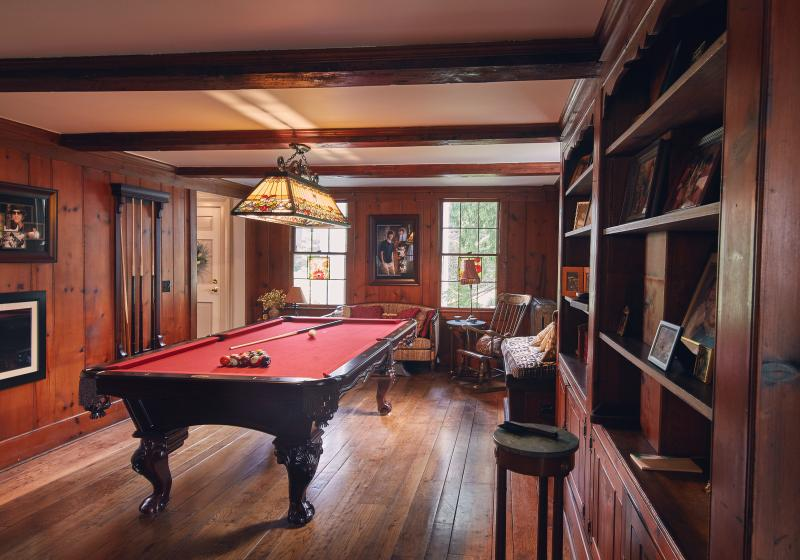 Billiards room with bar and fireplace at other end of room.