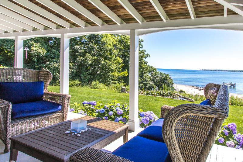 Front porch overlooks yard and beach