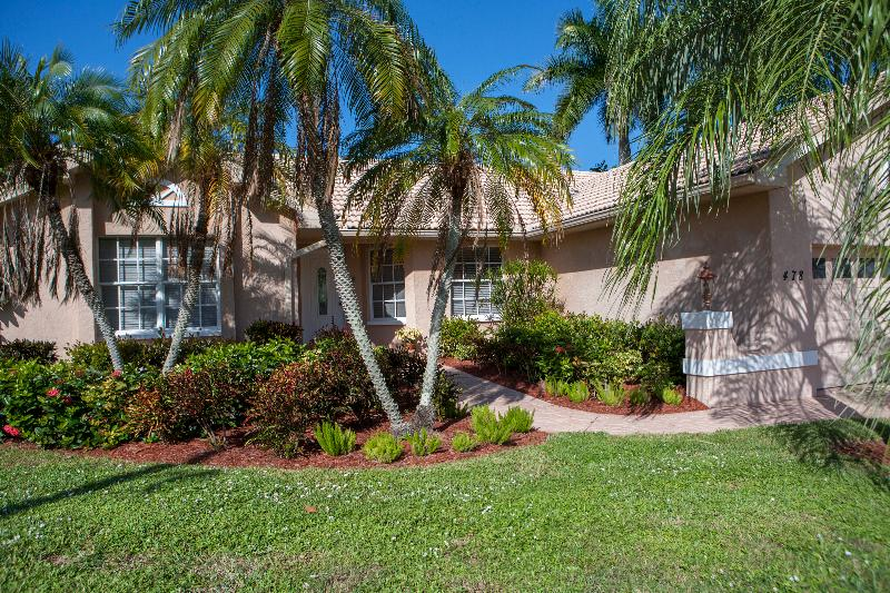 Front of Picture perfect palm trees and professionally landscaped greenery welcome you home.House.