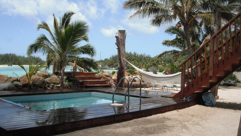 The swimming pool area is between the house and the beach.