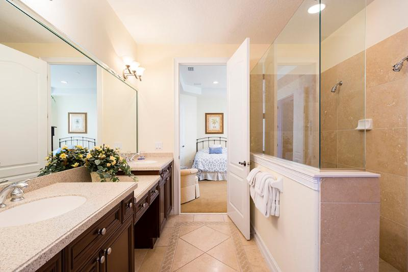 Bathroom ensuite with double shower and twin vanities.  Leads out to pool.