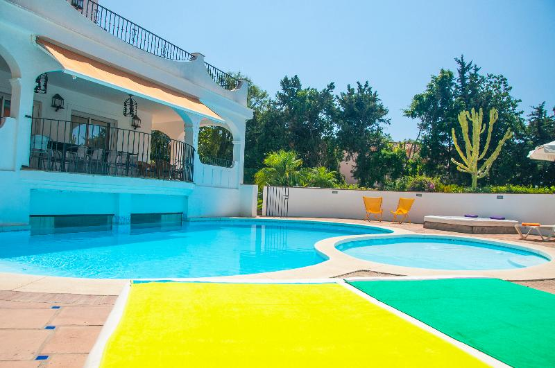 Sun beds by the swimming and children pools with garden views