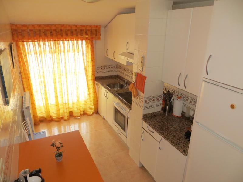 Vista de la cocina con mesa desplegable y cuatro sillas y acceso de por la cocina a la terraza.