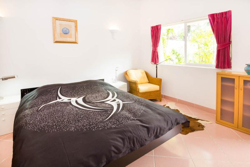 King size bed in guestroom 404/69 with 2 night tables, 2 night table lamps and seat beside window