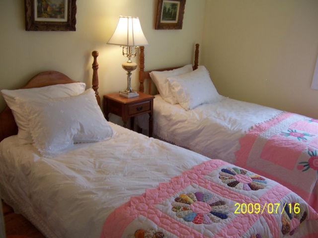 Duas camas, com edredões e colchas feitas à mão.