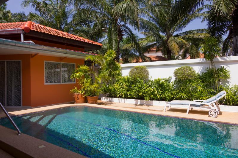 Ver en jardín con pared de 2,25 metros de alto que rodea la propiedad entera y cama para tomar sol