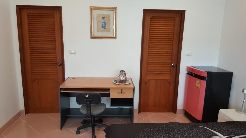 Pequeña oficina con hervidor de agua y silla de oficina entre puerta a vestidor y baño
