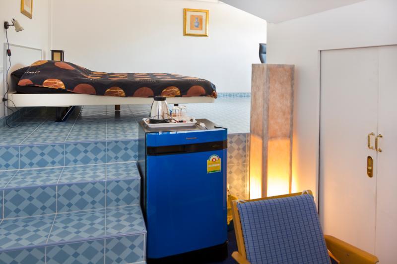 Vista sul secondo, camera leggermente sopraelevata della parte superiore-camera, con frigorifero, bollitore, scale e letto