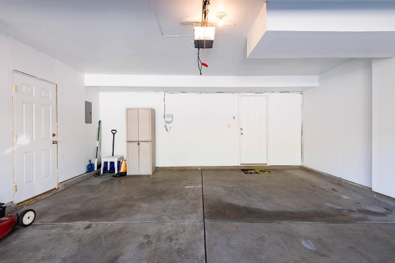 2 car garage with entry to lower living room and outside