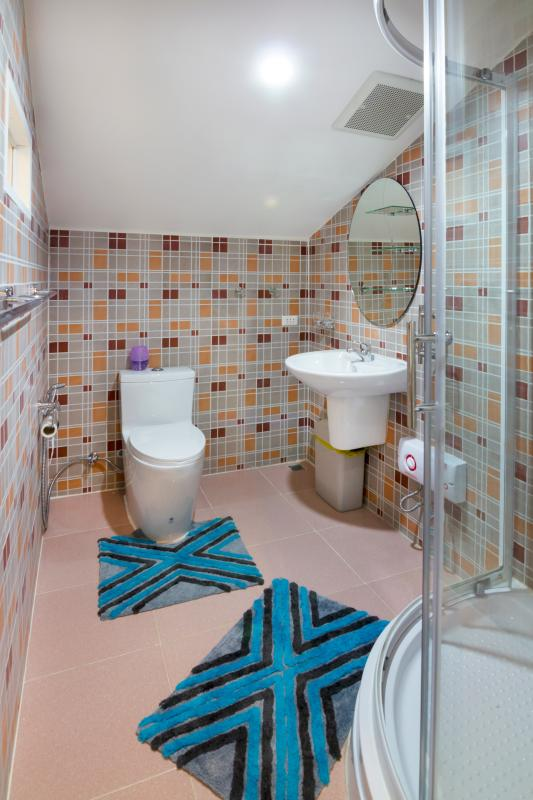 View into private bathroom of Top-guestroom with toilette, hand wash with cold and hot water+ mirror