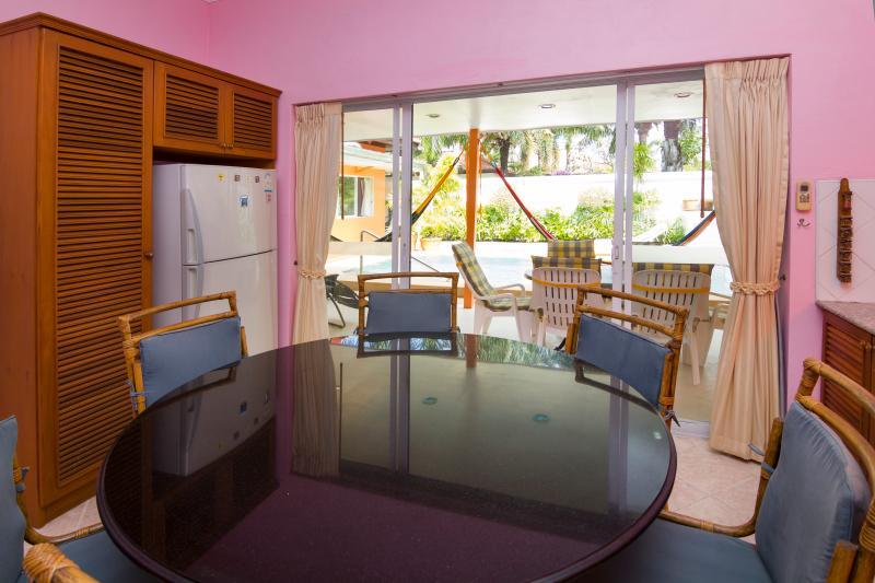 Grande tavolo all'interno di cucina con 6 sedie e armadio con grande frigorifero e freezer