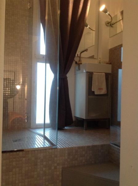 Bagno completo di doccia con cabina in cristallo, piastrelle in ceramica, finestra su giardino inter