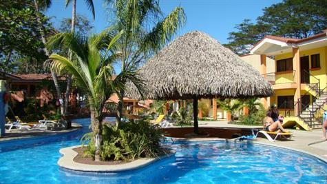 View of Cocomarindo pool with thatched roof pool bar