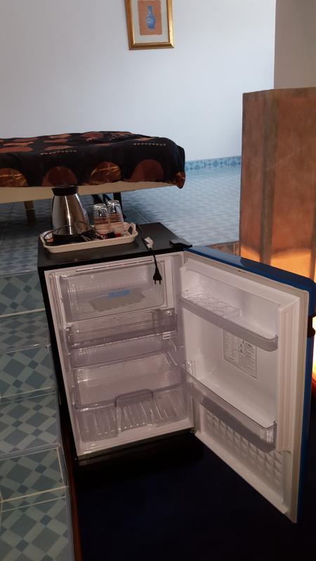 Refrigerator with door opened in first room of Top-guestroom 404/69 and water kettle