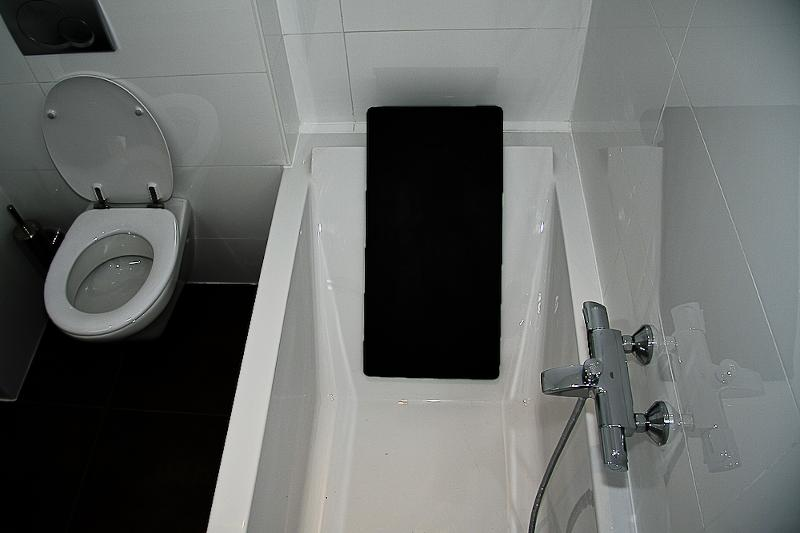 Bathroom with bathtub. Hand shower and extra toilet.