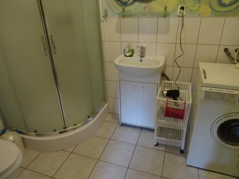 Bathtube, washer, hairdryer in the bathroom.