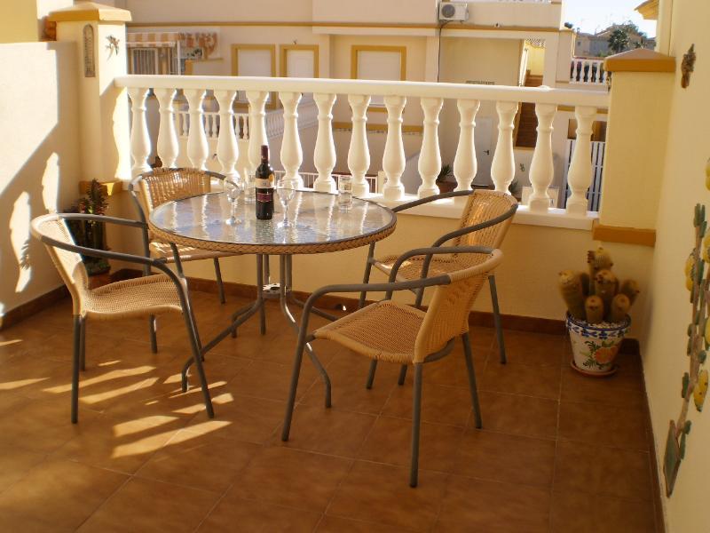 terraza de arriba, recién amueblada con mesa y sillas de plástico blanco