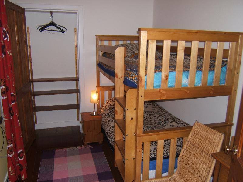 Twin room with bunk beds, with hanging cupboard & shelves.