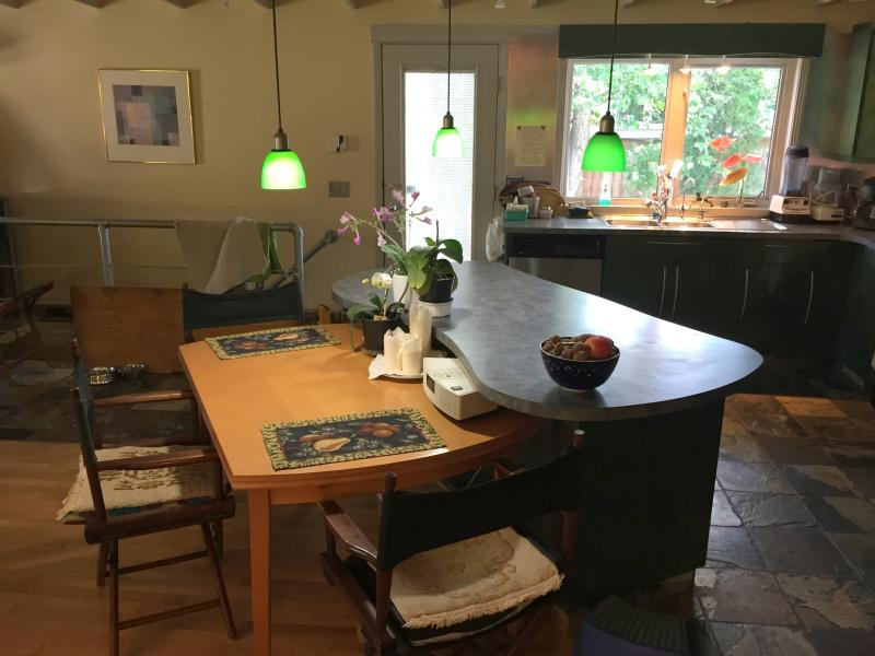 Open concept kitchen, dining, back door, stairwell.