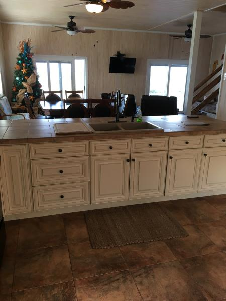 kitchen sink plus breakfast bar on other side with 4 stools