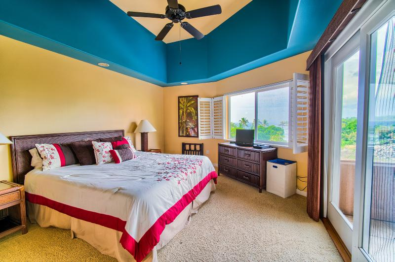 The master bedroom has vaulted ceilings and a stunning ocean view of Kahaluu!