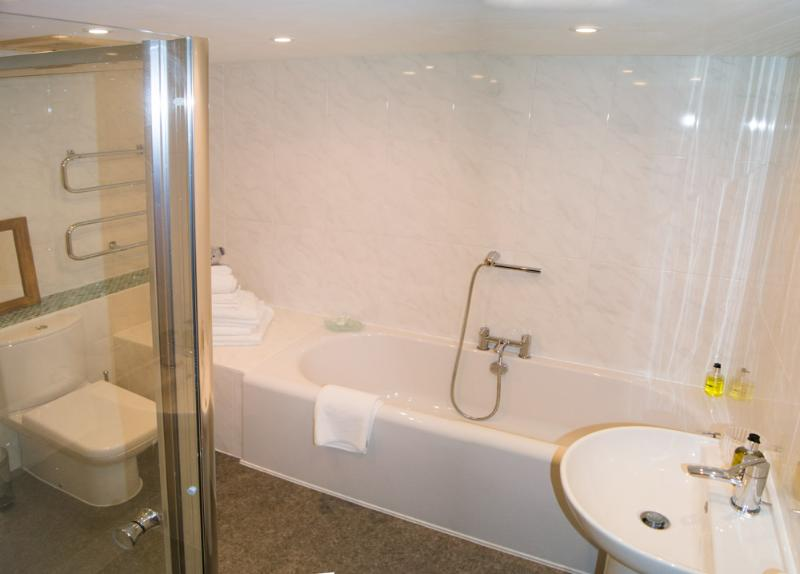 Large bathroom with double ended bath, large separate shower and heated towel rail.