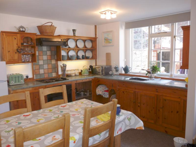 The dining area features a large table and handmade cupboards.
