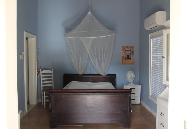 la habitación con cama queen size y baño privado, nevera pequeña