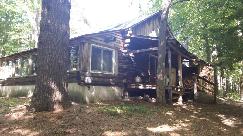 Log cabin with enclosed side porch, porch off living room and small deck off bedroom.