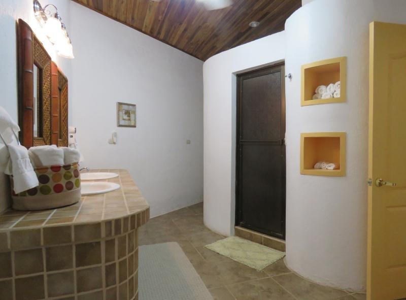 Large bathroom with double sinks, walk-in shower and separate room with toilet.