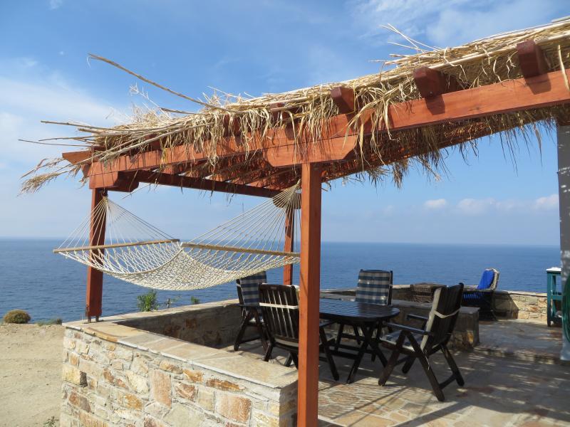 Véranda couverte avec vue sur la mer, hamac et table à manger, table basse, chaises longues