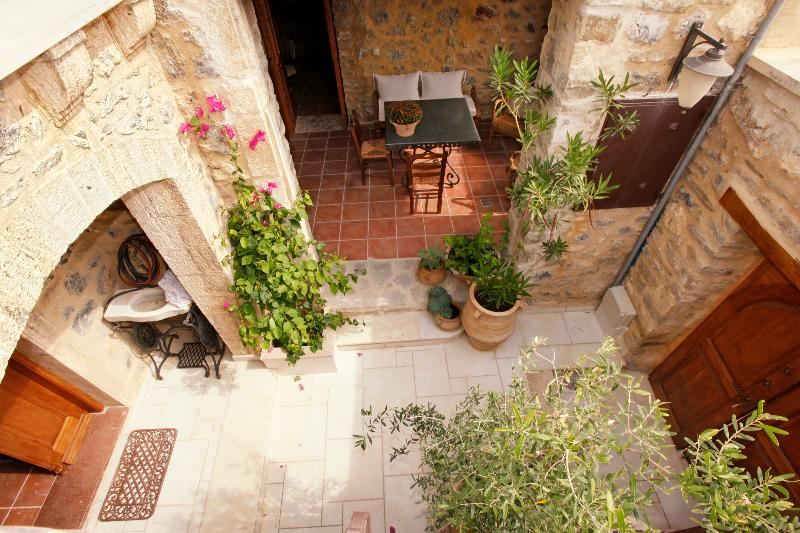 View of the patio and courtyard from the exterior stone stair to the upper level
