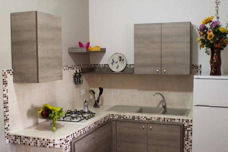 área de cocina con muebles de interior con toda la vajilla