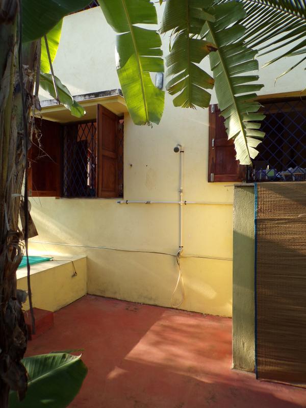 La ducha en el jardín está al lado de la piscina.