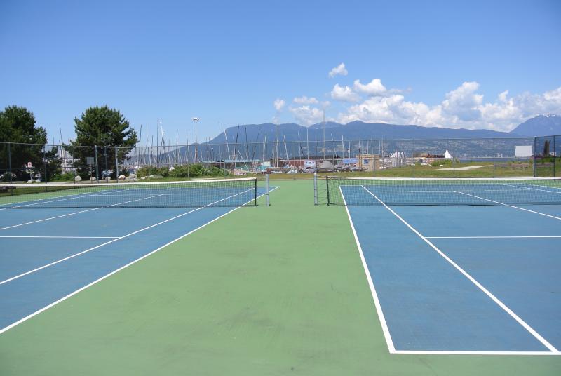 Jericho beach tenis con vistas a las montañas y el agua.
