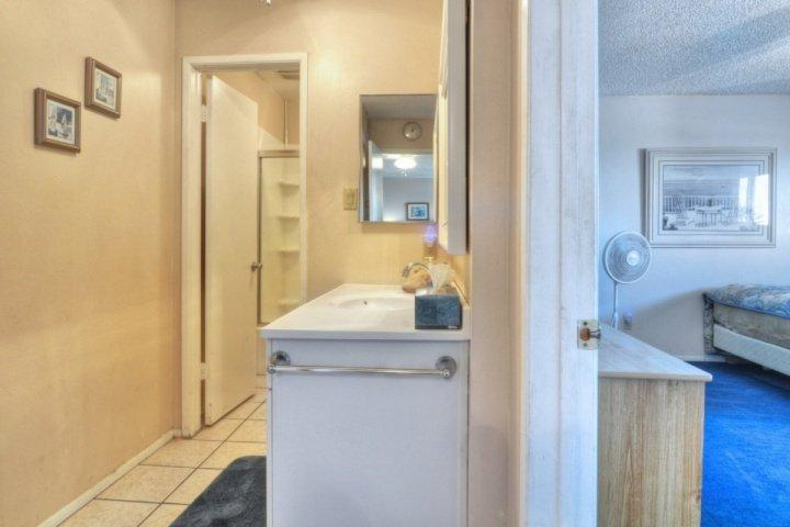 Hallway to bathroom with tub and shower and bedroom