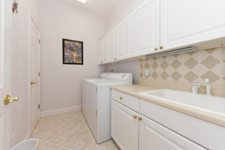 Laundry room with full size washer, dryer and utility sink.