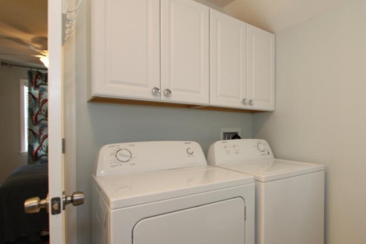 sala de lavado con lavadora / secadora ubicada en entre los dos dormitorios