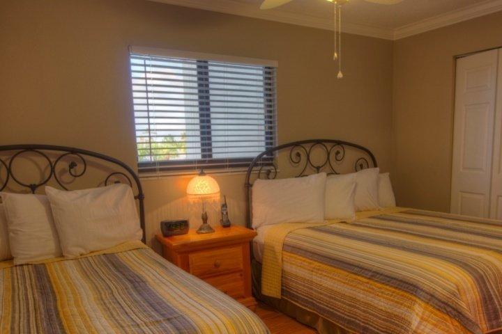 Dormitorio de invitados con reina y camas de tamaño completo