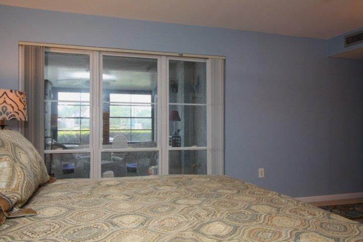 Slaapkamer met een uitzicht op het water met inbegrip van de patio