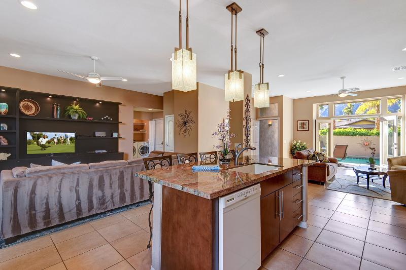 Center island kitchen with view to pool, living room and entertainment room. A large open floor plan