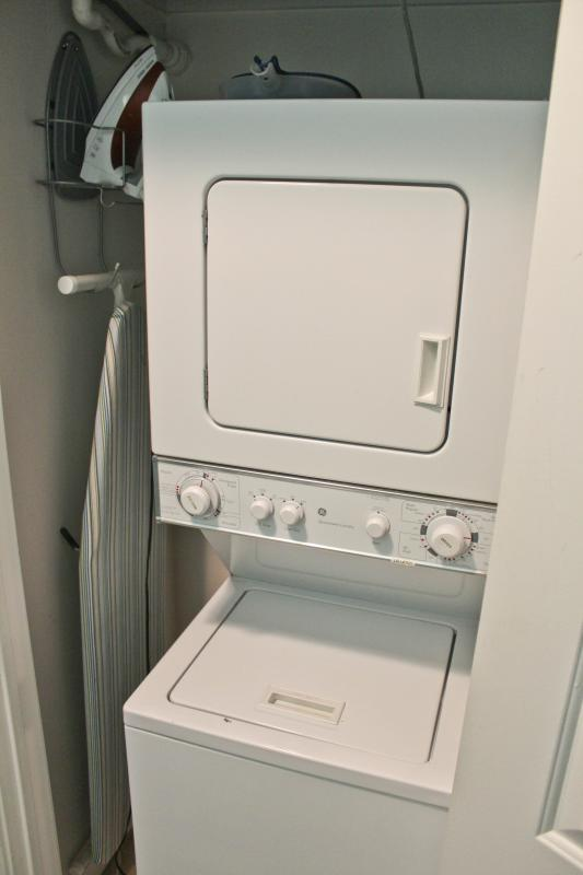 Washer/Dryer in the hallway with an iron and ironing board.