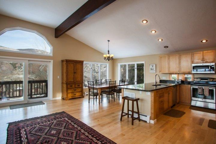 Views of kitchen, dining table that seats 6 and access to large wrap around deck with gas grill and mountain views.