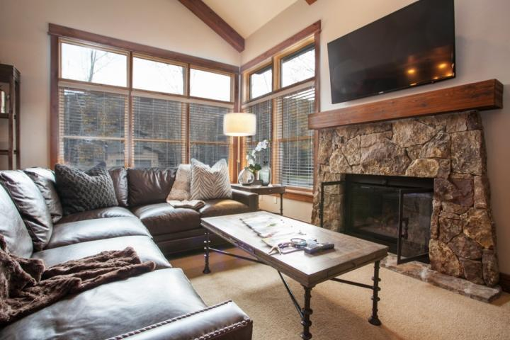 View of living room features gas fire place, flat screen TV and plenty of comfortable seating.