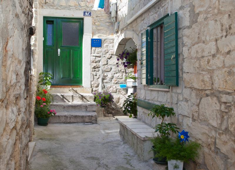 Courtyard in front of the apartment entrance with a stone bench where you can sit and relax