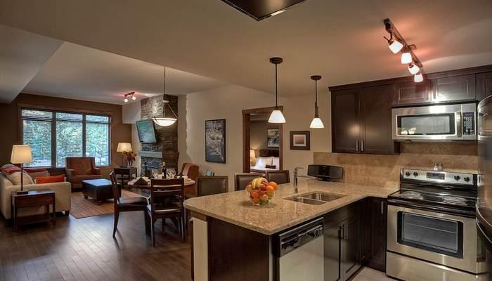 This chic condo features a sleek kitchen with high-end appliances and a breakfast bar