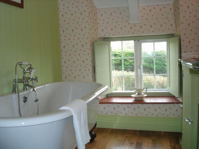 Traditional cottage bathroom with large roll top bath and vanity unit